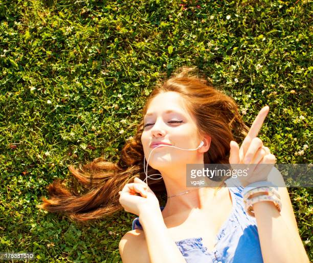 Happy Young Woman Lying on grass and listening music.