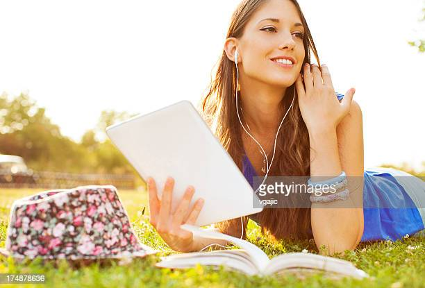 Happy Young Woman lying on grass and using digital tablet