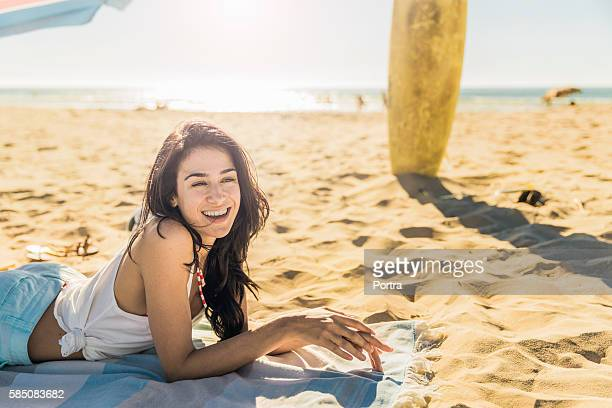 Happy young woman lying on shore at beach