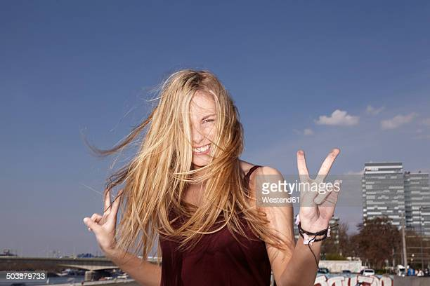 Happy young woman making peace sign