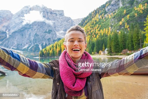 Happy young woman making selfie on lake braies, italy : Stock Photo