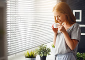 Happy young woman meets   morning with cup of coffee at window home
