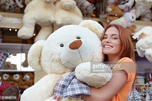 Happy young woman on a funfair hugging large teddy bear