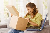 Happy young woman opening package at home