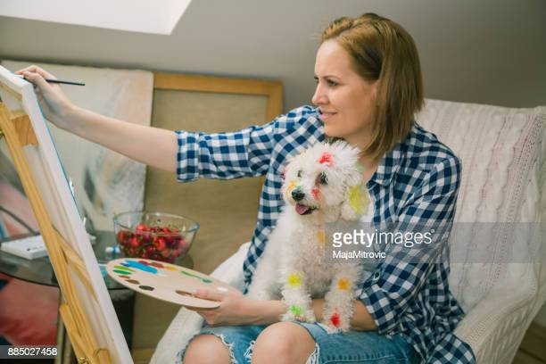Happy young woman paints on canvas