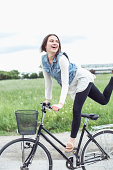 Happy young woman performing trick on bicycle at countryside