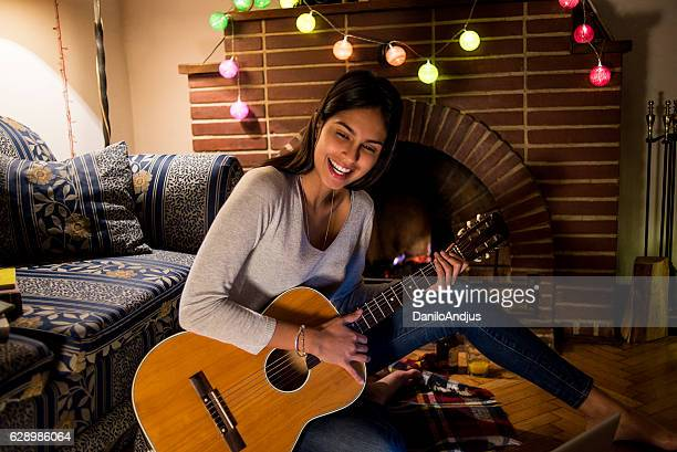 happy young woman playing the guitar at home