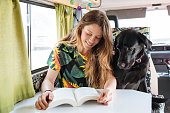 happy young woman reading a book and playing with her dog in a camper van