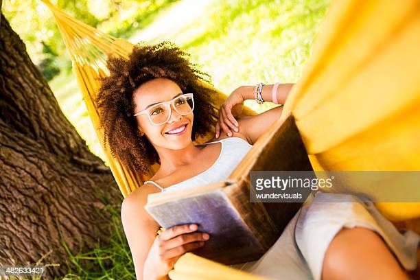 Feliz joven mujer descansando en una hamaca