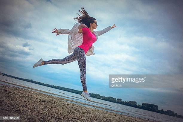 Glückliche junge Frau Laufen und Springen am Strand