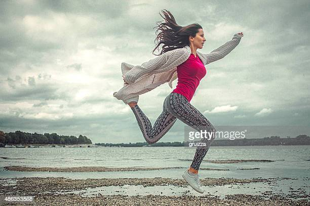 Happy young woman running and jumping on the beach