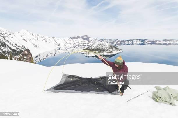 Glückliche junge Frau setzt Zelt im Schnee mit Blick auf massive See