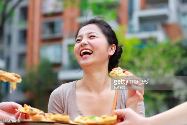 happy young woman share pizza with friends