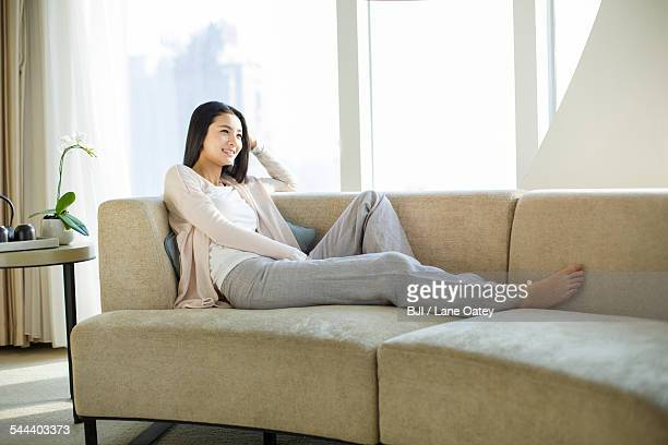 Happy young woman sitting by window
