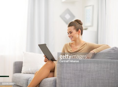 happy young woman sitting on divan and using tablet pc : Stock Photo