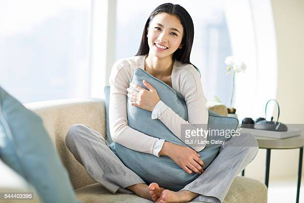 Happy young woman sitting on sofa