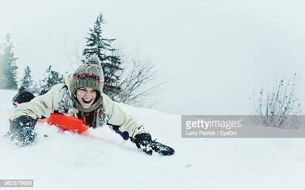 Happy Young Woman Sledding On Snowcapped Mountain During Winter