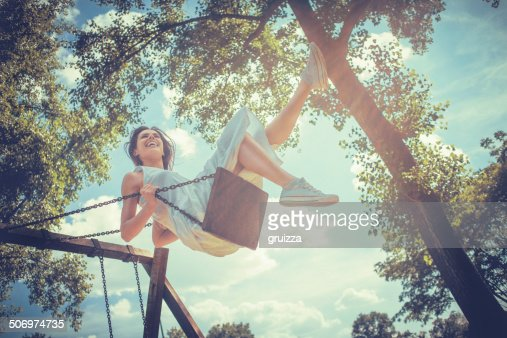 Happy young woman smiling on swing