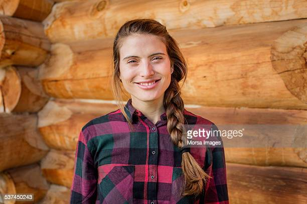 Happy young woman standing against log cabin