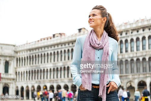 Happy young woman standing on piazza san marco in venice : Stock Photo