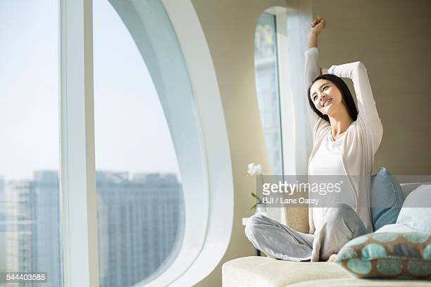 Happy young woman stretching arms on sofa