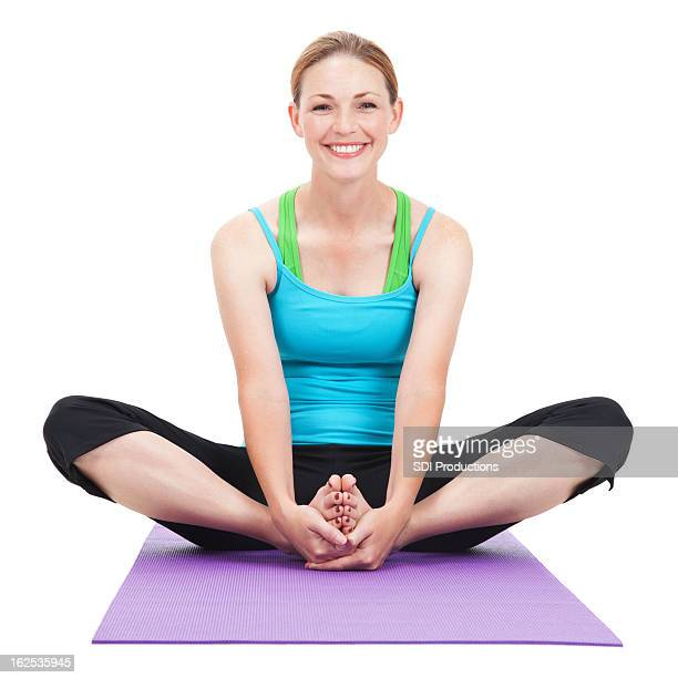 Glückliche junge Frau Dehnung Beine auf Yoga-Matte