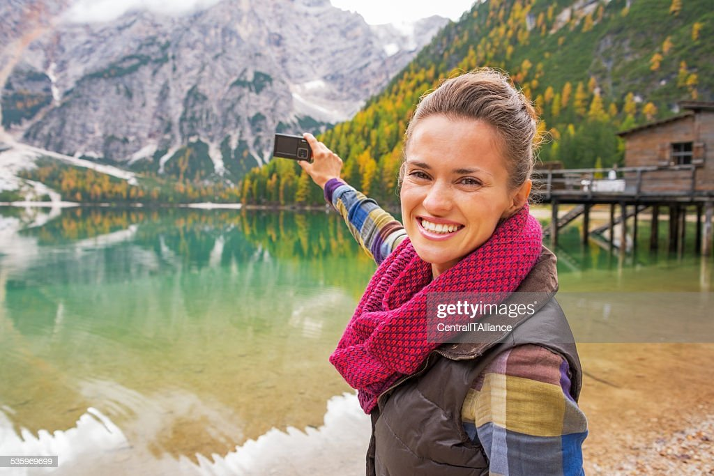 Happy young woman taking photo on lake braies, italy : Stock Photo