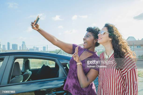 Happy young woman taking selfie with female friend by car against sky, Los Angeles, California, USA