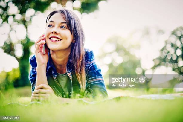 Happy young woman talking on smart phone in park