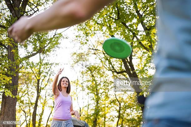 幸せな若い女性の投げる friesbee いたします。