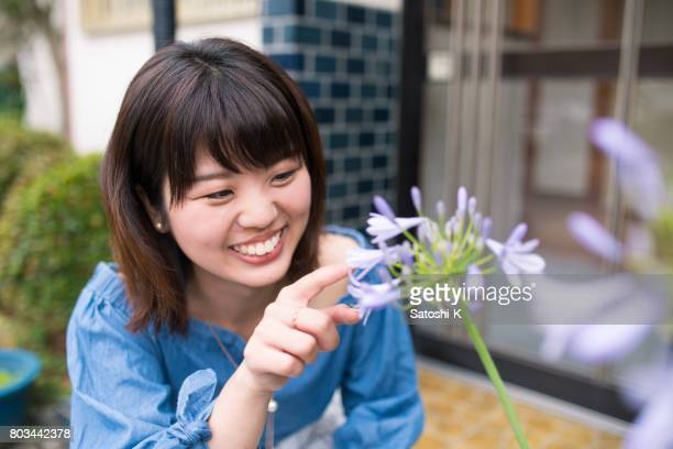 Happy young woman touching african lily