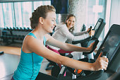 Happy young Caucasian woman wearing sport clothes, training on exercise bike in gym. Smiling woman cycling exercising bike in background