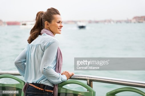 Happy young woman travel by venice water bus : Stock Photo