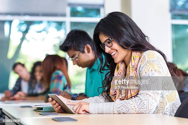 Happy young woman using digital tablet during college class