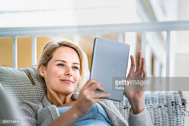 Happy young woman using digital tablet on balcony