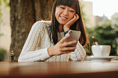 Happy young woman sitting at outdoor cafe and using her cellphone. Female model reading text message on smart phone at coffee shop  and smiling.