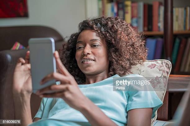 Felice giovane donna utilizzando il telefono cellulare sul divano