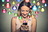 communication technology mobile high tech concept. Closeup happy young woman using texting on smartphone with social media application symbols icons flying out of screen isolated on grey background.