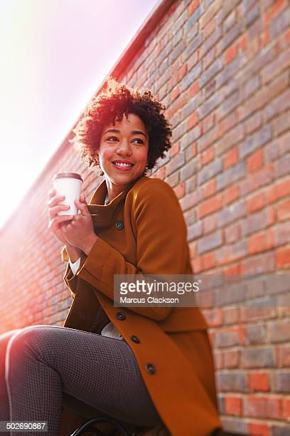 Happy young woman waiting holding a coffee