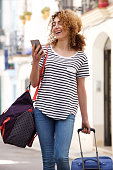 Portrait of happy young woman walking in city with bag and mobile phone