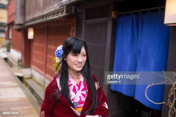 Happy young woman walking in Higashi Chaya district in Kanazawa, Japan