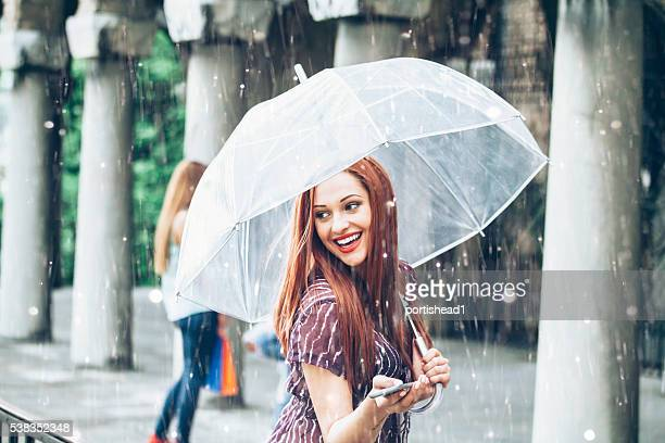 Happy young woman walking with umbrella under the rain