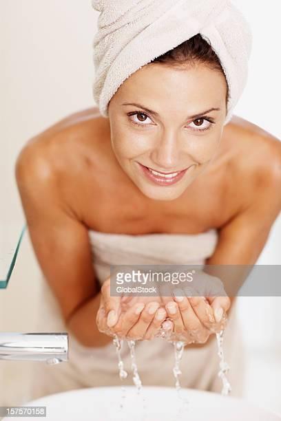 Heureuse jeune femme laver son visage avec de l'eau