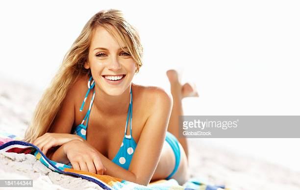 Happy young woman wearing a blue polka dot bikini on beach