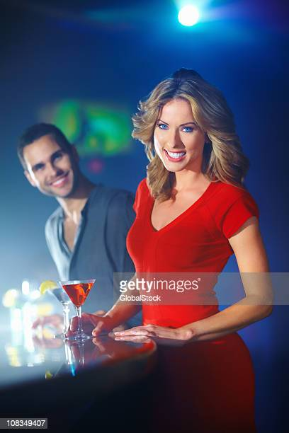 Happy young woman with a cocktail and man in background