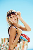 Happy young woman with beach bag on a vacation