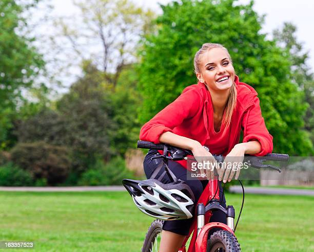 Happy young woman with bicycle in a park