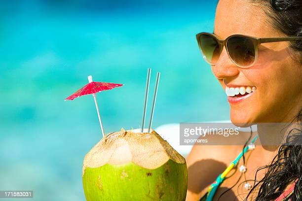 Glückliche junge Frau mit Kokosnuss-drink im tropischen türkisfarbenen Strand