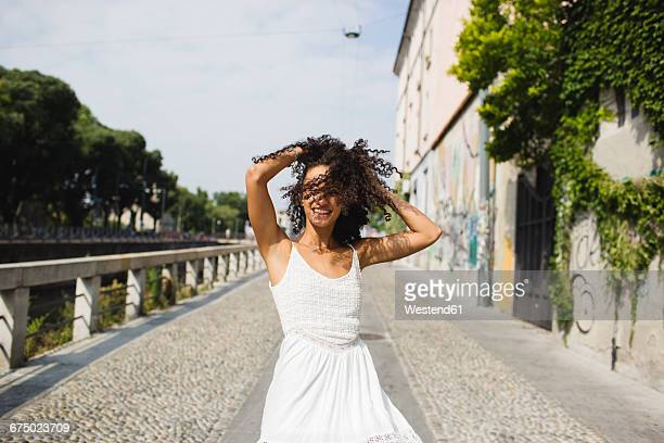 Happy young woman with hands in her hair dancing on the street