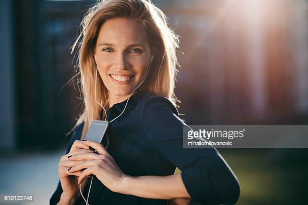Happy young woman with headphones enjoying the day